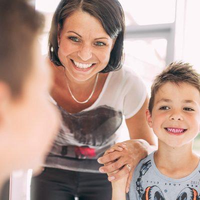 Mutter hält Jungen an der Hand, dessen Zähne angefärbt wurden