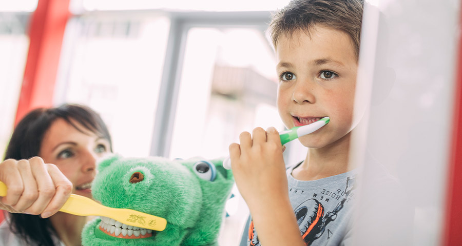 Junge putzt sich die Zähne mit Zahnbürste, Mutter guckt zu