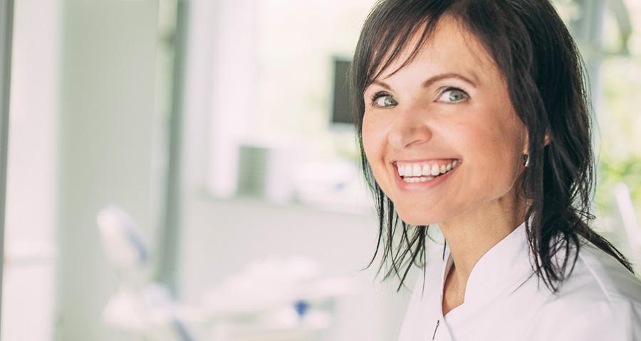 Mitarbeiterin lacht mit schönen ästhetischen Zähnen