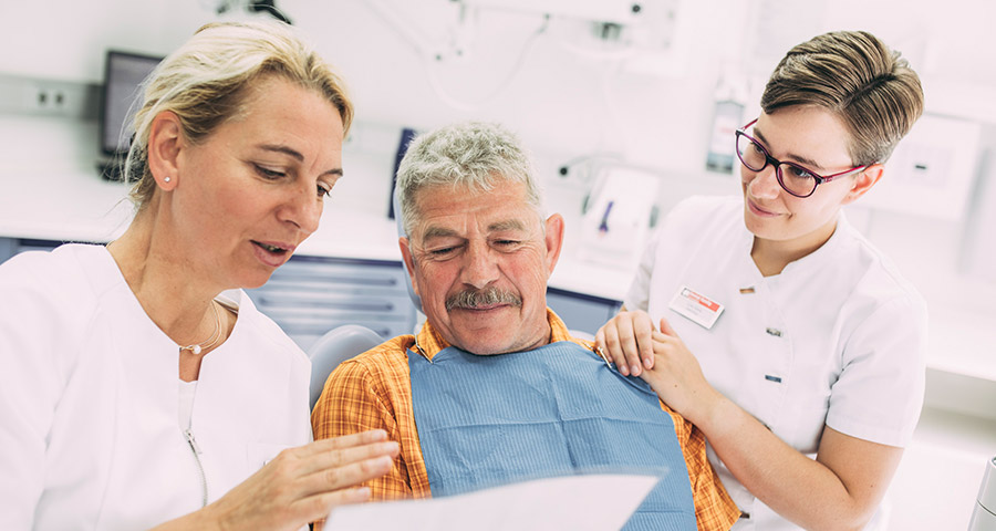 Dr. Carmen Pohl und Mitarbeiterin beraten Patienten über amalgamfreien Zahnersatz