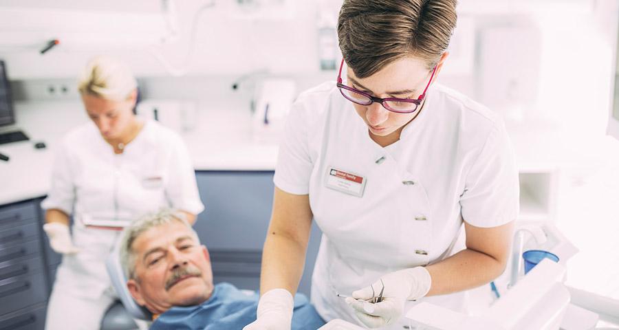 Mitarbeiterin bereitet Instrumente für Behandlung vor