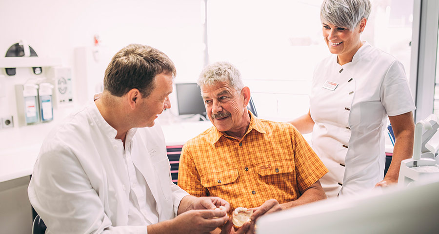 Dr. Andreas Pohl erklärt Patienten die Behandlungsmethode Feste Zähne