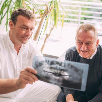 Dr. Andreas Pohl erklärt Patienten auf Röntgenbild Implantatverlust
