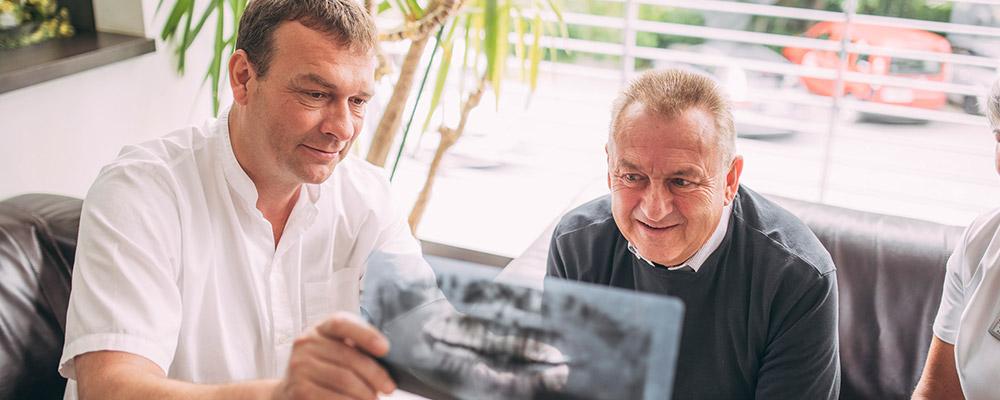 Dr. Andreas Pohl zeigt Patienten Röntgenbild