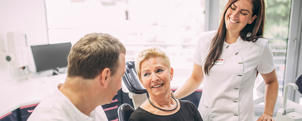 Dr. Andreas Pohl spricht mit lächelnder Dame, Mitarbeiterin freut sich im Hintergrund