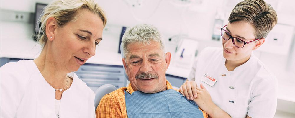 Dr. Carmen Pohl und Mitarbeiterin beraten Patient zu Wurzelbehandlung