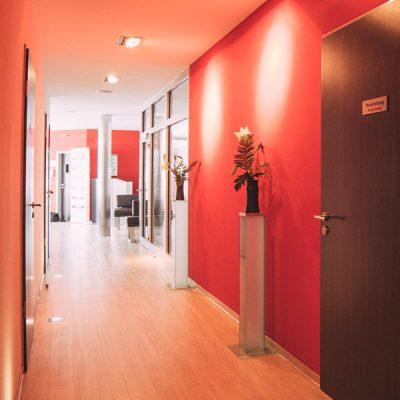 langer Flur mit Behandlunstüren, roten Wänden und Pflanzen