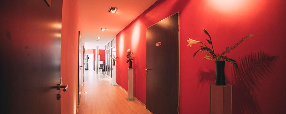 langer Flur mit roten Wänden und Pflanzen