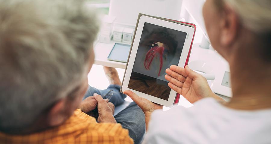 Dr. Carmen Pohl erklärt Patienten Wurzelspitzenresektion auf Tablet