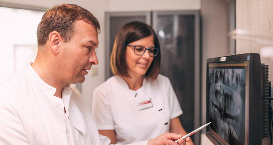 Dr. Andreas Pohl und Mitarbeiterin schauen sich Röntgenaufnahmen von Gebiss an