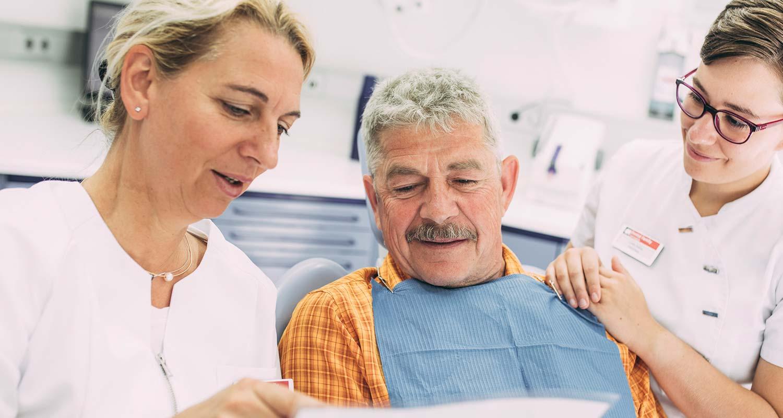 Dr. Carmen Pohl und Mitarbeiterin erklären Patienten etwas über Erkrankungen des Zahnfleischs