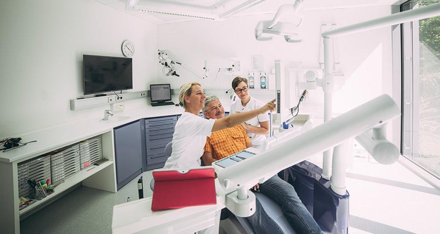 Dr. Carmen Pohl erklärt Patienten etwas auf dem Bildschirm
