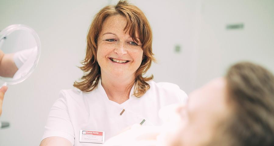 Mitarbeiterin lächelt Patienten freundlich zu