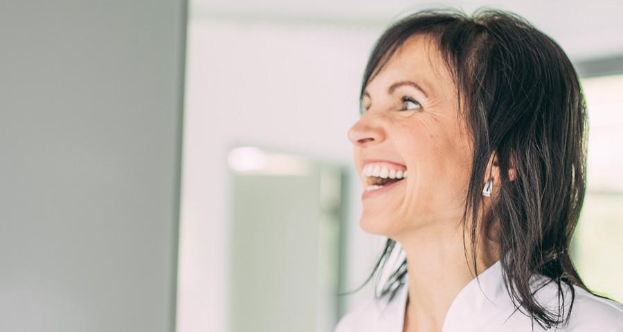 Mitarbeiterin mit weißen Zähnen lächelt