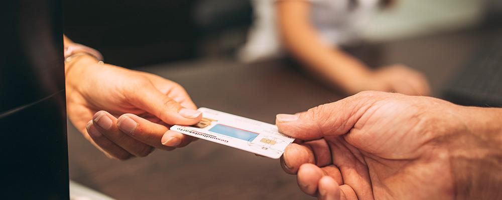 Patient gibt Mitarbeiterin Versicherungskarte