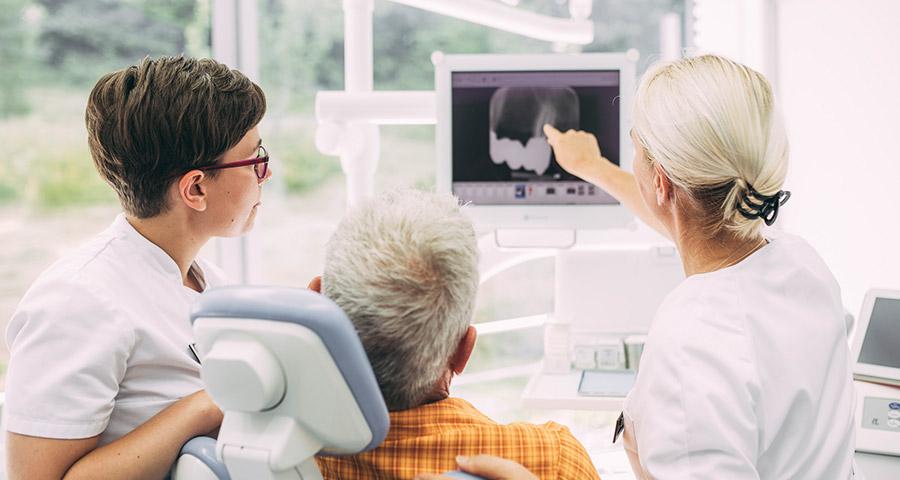 Dr. Carmen Pohl zeigt Patient auf Röntgenbild entzündete Zahnwurzel