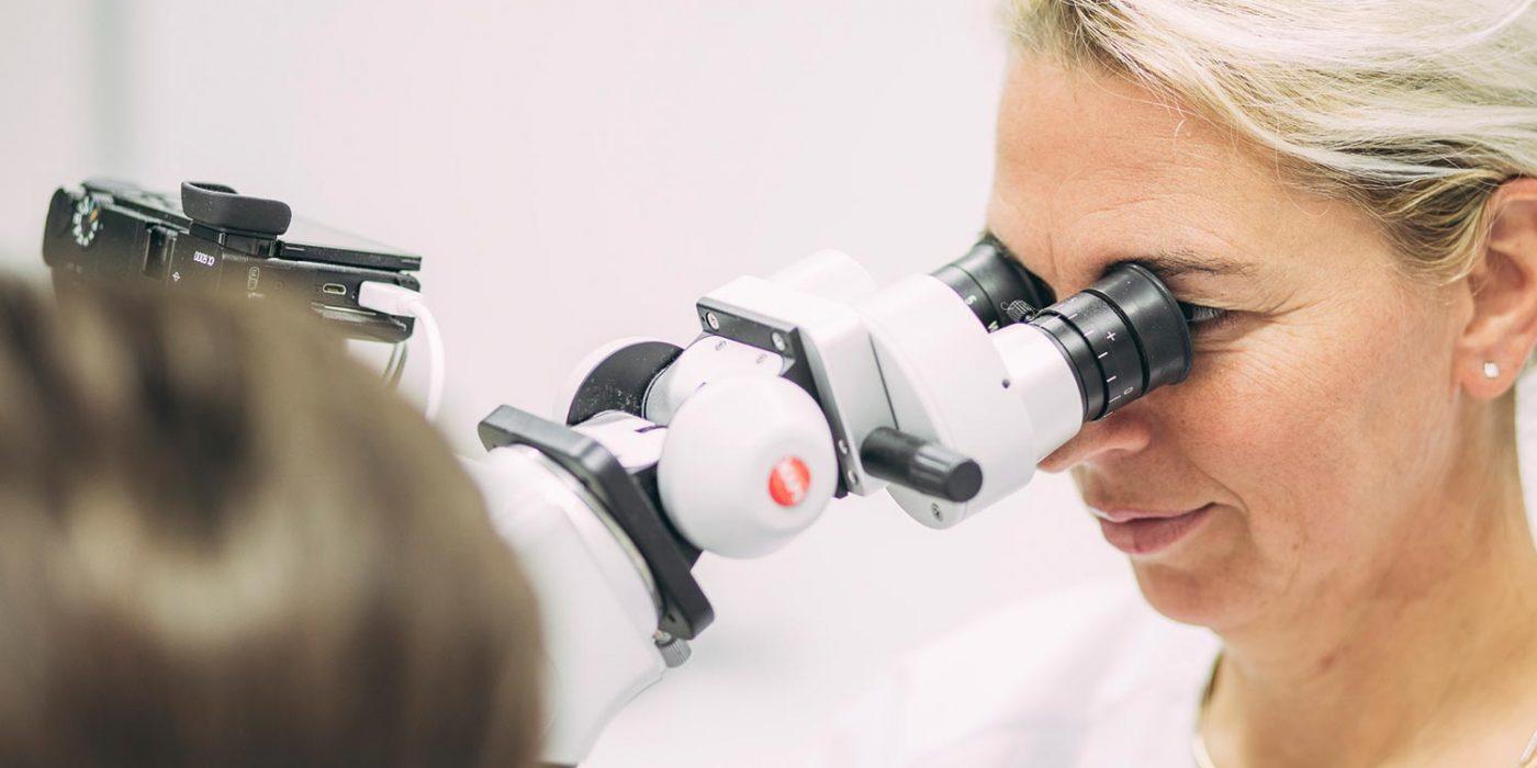 Dr. Carmen Pohl schaut durch Mikroskop