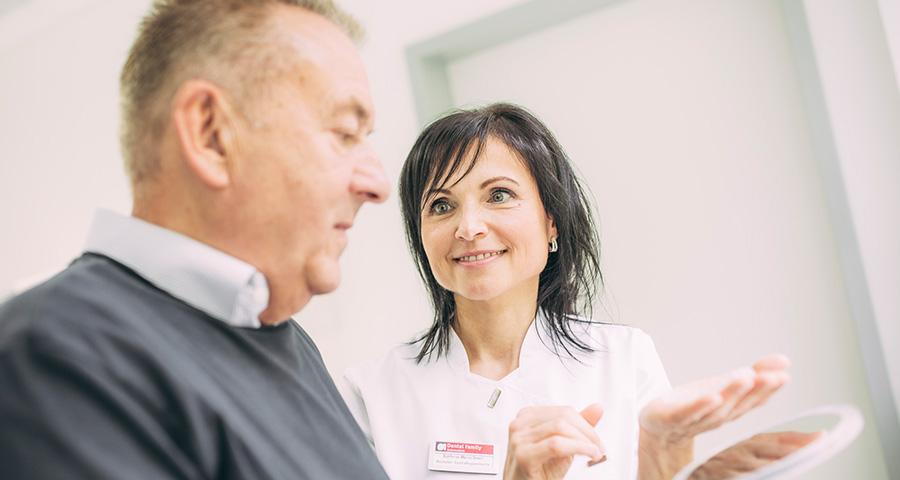 Mitarbeiterin zeigt Patienten im Spiegel seine neuen Zähne