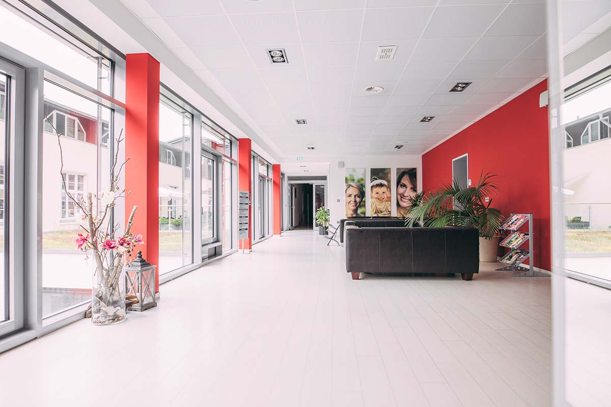 rote Wände und dunkle Sofas in den Praxisräumen