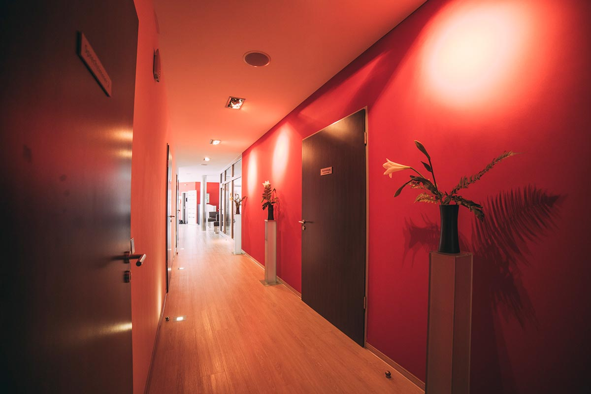Langer Flur mit roten Wänden und Türen zu den Behandlungszimmern