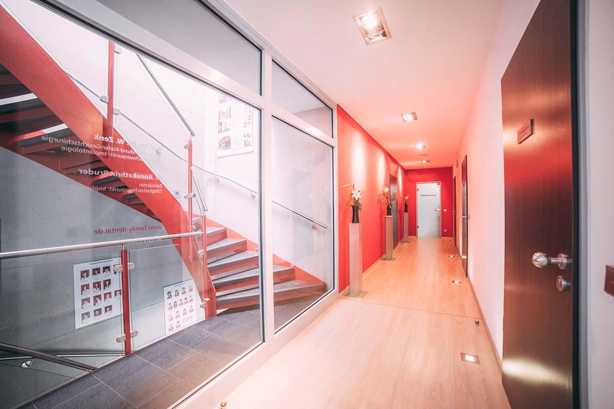 Langer Flur mit roten Wänden und roter Treppe