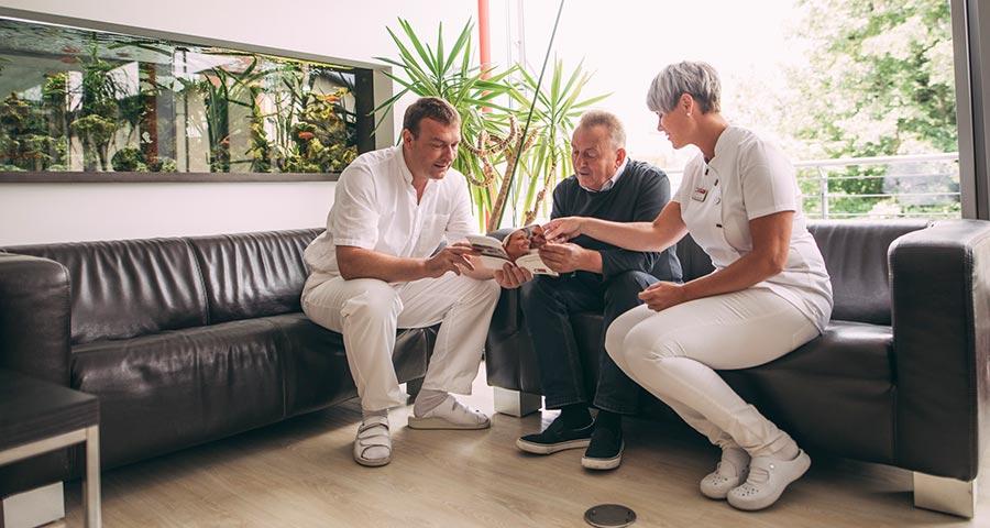 Dr. Andreas Pohl und Mitarbeiterin erklären Patienten die Möglichkeiten mit Zahnimplantaten