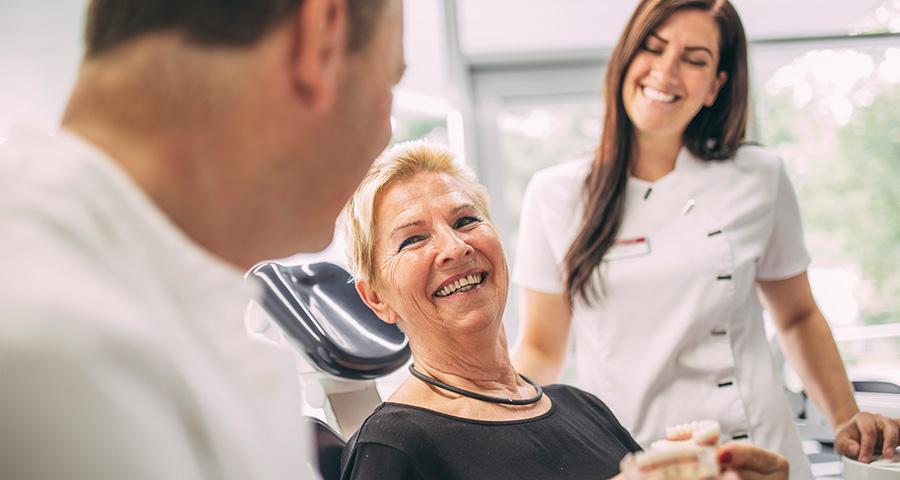 Patienten freut sich und lächelt Dr. Andreas Pohl an, Mitarbeiterin im Hintergrund lacht mit