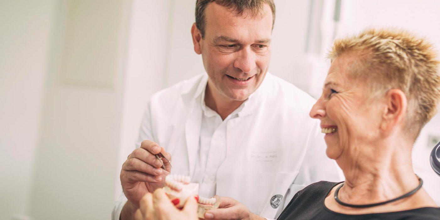 Dr. Andreas Pohl erklärt Patientin am Modell Zahnimplantate